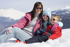 Mother with two daughters (6-8) sitting together in snow field, wearing sunglasses, smiling, portrait, mountain range in backgroun Royalty Free Stock Images