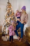 Mother with two daughters standing by the Christmas tree in a sweater. And a warm cap Stock Photos