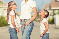 Mother and two daughters standing on the road Stock Images