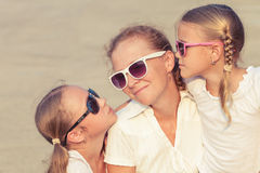 Mother and two daughters standing on the road at the day time. Stock Photo