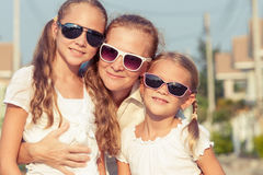 Mother and two daughters standing on the road at the day time. Royalty Free Stock Photo