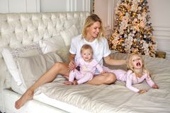 Mother with two daughters in their pajamas sitting on the bed. In the new year Royalty Free Stock Photography