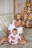 Mother with two daughters in their pajamas sitting on the bed. In the new year Stock Photos