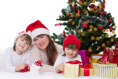 Mother and two daughters under Christmas tree Royalty Free Stock Photo