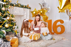Mother and two daughters unpack gifts on New Year 2016. Stock Photos