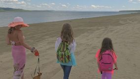 Mother with two daughters is walking along the beach. Woman on a leash has two little dogs toy terrier. Teenager and kid. The girl has a hat, and the children stock video footage