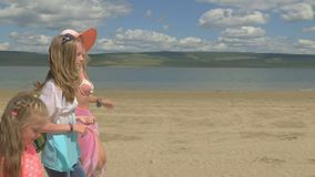 Mother with two daughters is walking along the beach. Woman on a leash has two little dogs toy terrier. Teenager and kid. The girl has a hat, and the children stock footage