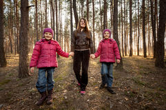 Mother and two daughters walking at sunny forest Royalty Free Stock Photo
