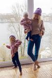 Mother with two daughters in warm clothes standing. By the large window Royalty Free Stock Photo