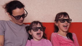 Mother with two daughters watching movie in 3D glasses on the couch. Family watching 3D film on an orange couch. stock video