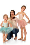 Mother and two daughters. A young mother with two daughters who dressed in ballet dresses - Isolated on white background Royalty Free Stock Images