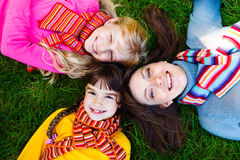 Mother and two girls. In bright scarves lying on the grass Royalty Free Stock Photography