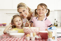Mother And Two Girls Baking In Kitchen Stock Photography