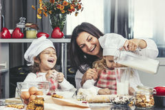 Mother and two happy little baby girl drinking milk and cook at. The table in the kitchen is lovely and beautiful Royalty Free Stock Photos