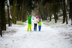 Mother and two her sons cheerfully spend time in winter park. Stock Photo