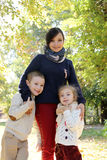 Mother with two kids in autumn park Royalty Free Stock Photos