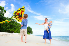 Mother and two kids flying kite Stock Photos