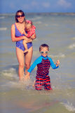 Mother with two kids having fun in summer sea Stock Photography