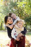 Mother and two kids hugging in autumn park Stock Image
