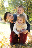 Mother with two kids hugging in autumn park Royalty Free Stock Image