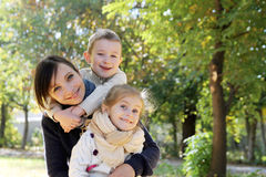 Mother and two kids hugging in autumn park Royalty Free Stock Photos