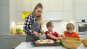 Mother and two kids making pizza with basil. Leaves in the kitchen stock footage