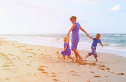 Mother and two kids play on beach Stock Photos