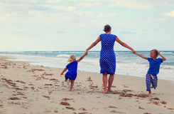 Mother and two kids play on beach Royalty Free Stock Photos
