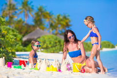 Mother and two kids playing with sand on tropical. Mother and two girls playing with sand on tropical beach Royalty Free Stock Photos