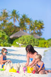Mother and two kids playing with sand on tropical Royalty Free Stock Photography