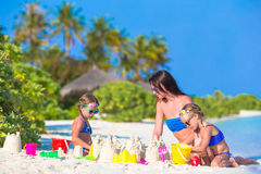 Mother and two kids playing with sand on tropical. Mother and two girls playing with sand on tropical beach Stock Photography