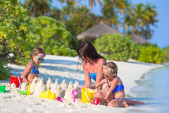 Mother and two kids playing with sand on tropical. Mother and two girls playing with sand on tropical beach Royalty Free Stock Photo