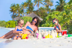 Mother and two kids playing with sand on tropical. Mother and two girls playing with sand on tropical beach Royalty Free Stock Photography