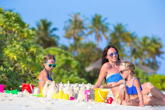 Mother and two kids playing with sand on tropical Stock Photos