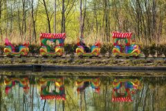 Mother and two kids riding a colorful carousel train in the spring park, reflection in a lake Royalty Free Stock Photography