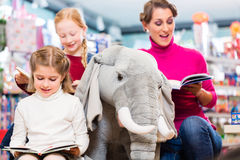 Mother with two kids shopping in toy store. One girl sitting on a plush elephant, one reading a book Royalty Free Stock Photo