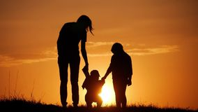 Mother and two kids silhouettes at sunset. Concept of friendly family. Mother and two kids silhouettes at sunset. Concept of friendly family stock video