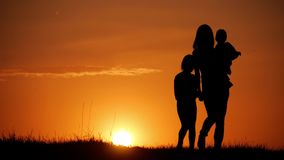 Mother and two kids silhouettes at sunset. Concept of friendly family. Mother and two kids silhouettes at sunset. Concept of friendly family stock footage