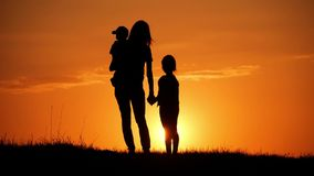 Mother and two kids silhouettes at sunset. Concept of friendly family. Mother and two kids silhouettes at sunset. Concept of friendly family stock video footage
