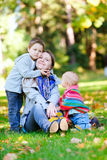 Mother and two kids sitting on grass. At sunny autumn day royalty free stock photography
