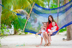 Mother and two kids sitting on hammock at tropical beach Stock Photo