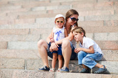 Mother and two kids sitting on steps Stock Image