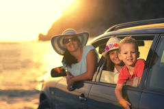 Mother with two kids travel by car on summer vacation sunset. Selective focus Stock Photography