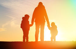 Mother and two kids travel at sunset Royalty Free Stock Image