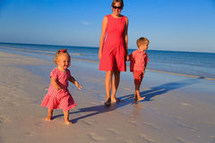Mother and two kids walking on beach Stock Images