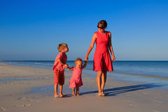 Mother and two kids walking on the beach Royalty Free Stock Image
