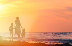 Mother and two kids walking on the beach at sunset Stock Photos
