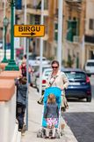 Mother and two kids walking in city center. Vertical photo of mother with her son and toddler daughter in stroller walking in city street in Malta Europe stock photo