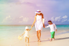 Mother and two kids walking on tropical beach Stock Images