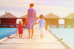Mother with two kids walking on tropical beach resort Royalty Free Stock Photography